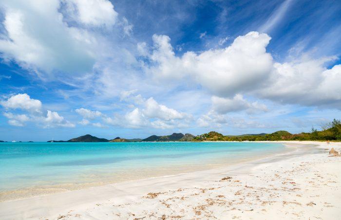 Wit strand en blauw water op Antigua en Barbuda