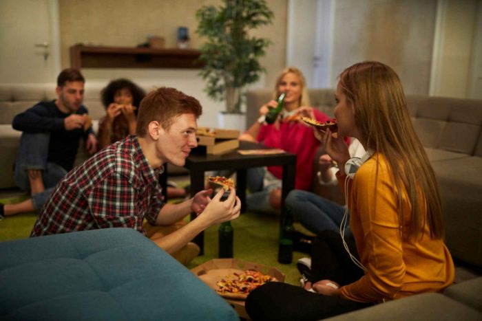 Groep vrienden eten pizza in een hostel