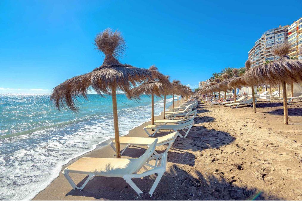 Strandbedden en helder blauwe zee bij Malaga