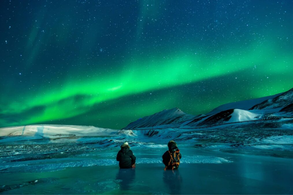 Backpackers op het ijs onder het Noorderlicht in Alaska